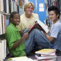 Drei Jungen zwischen Büchern | © panthermedia.net / Cathy Yeulet